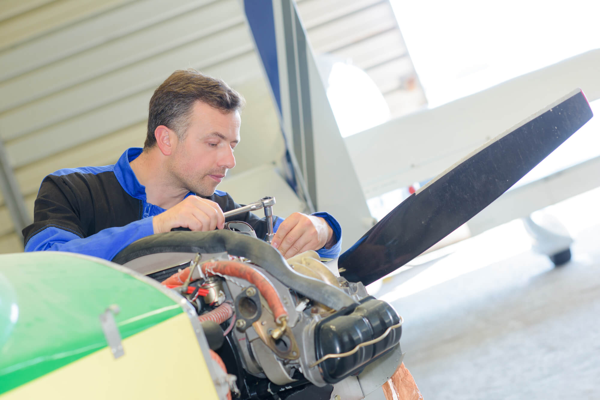 Mecânico de manutenção aeronáutica trabalhando com um motor pistão